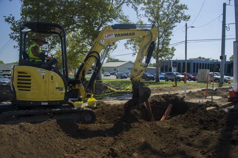 underground construction, man placing fiber optic cable